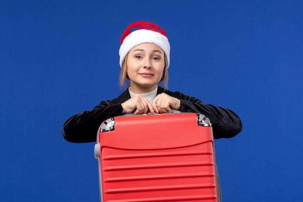 青い壁の色の新年の休日の休暇に大きな赤いバッグを運ぶ正面図若い女性