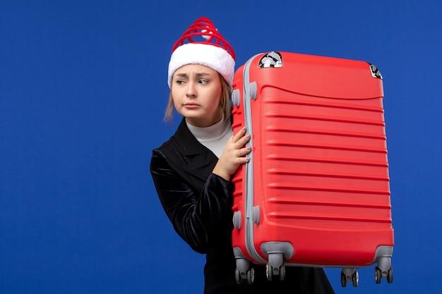 Вид спереди молодой леди, несущей большую красную сумку на синей стене цвета новогодних праздников, каникул