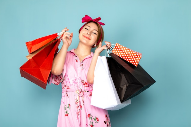 A front view young lady in flower designed pink dress posing holding shopping packages on blue