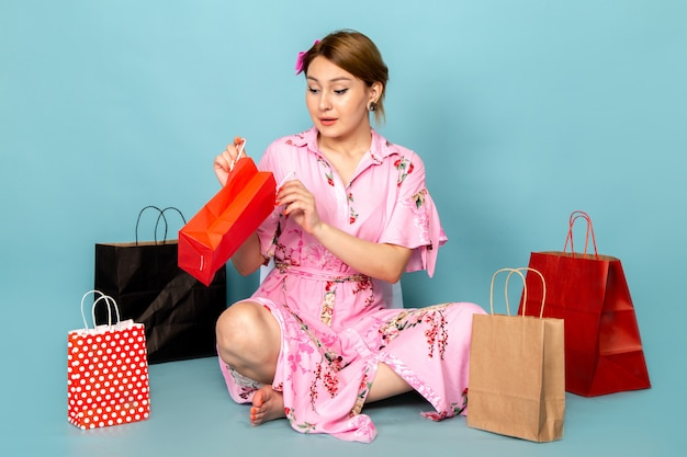 A front view young lady in flower designed pink dress sitting and posing with shopping packages on blue