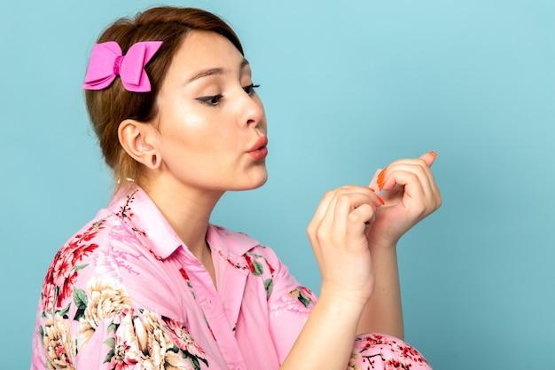 Una giovane signora di vista frontale in vestito dentellare progettato fiore che lavora con le sue unghie sull'azzurro