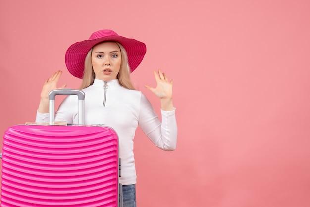 手を上げるピンクのスーツケースの後ろに隠れている正面図若い女性