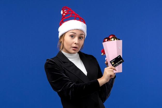 Vista frontale della giovane signora che tiene la carta di credito sui giocattoli di festa di emozione del nuovo anno della parete blu