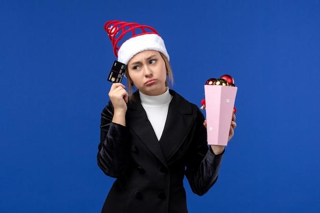 Вид спереди молодая дама держит банковскую карту на синей стене новогодние эмоции праздники