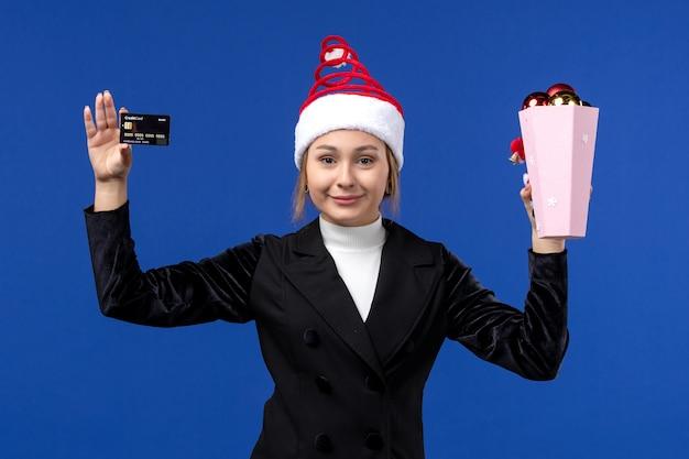 Вид спереди молодая дама держит банковскую карту на синей стене новогодние эмоции праздники игрушка
