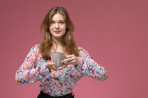 Вид спереди молодой леди, держащей чашку в руке