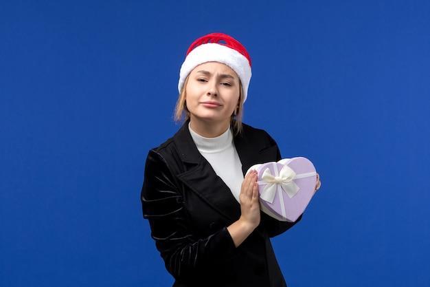 Giovane signora di vista frontale che tiene presente a forma di cuore sulle feste blu del regalo del nuovo anno della parete