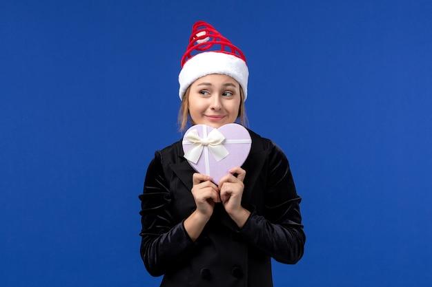 Giovane signora di vista frontale che tiene presente a forma di cuore sul regalo di festa del nuovo anno della parete blu