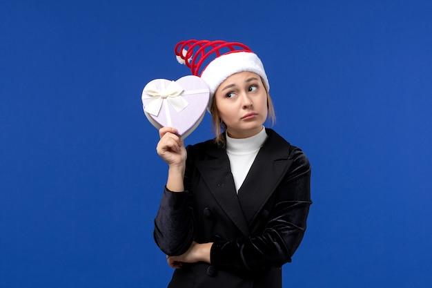 Giovane signora di vista frontale che tiene presente a forma di cuore sui regali di festa del nuovo anno della parete blu