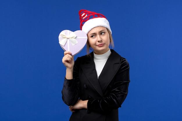Giovane signora di vista frontale che tiene presente a forma di cuore sul regalo di feste di capodanno della parete blu