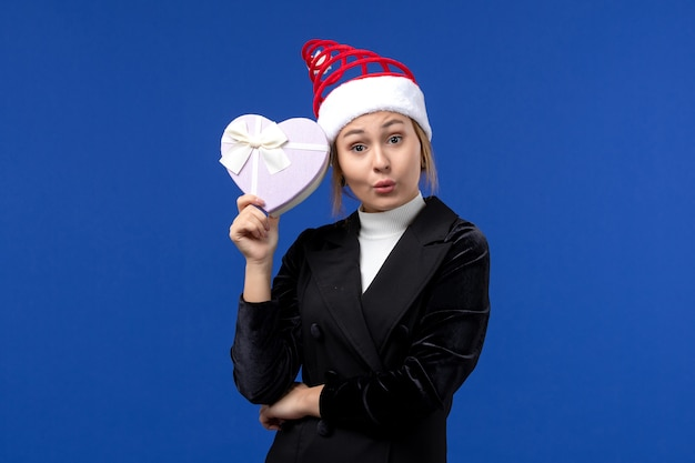 Giovane signora di vista frontale che tiene presente a forma di cuore sui regali di feste del nuovo anno della parete blu
