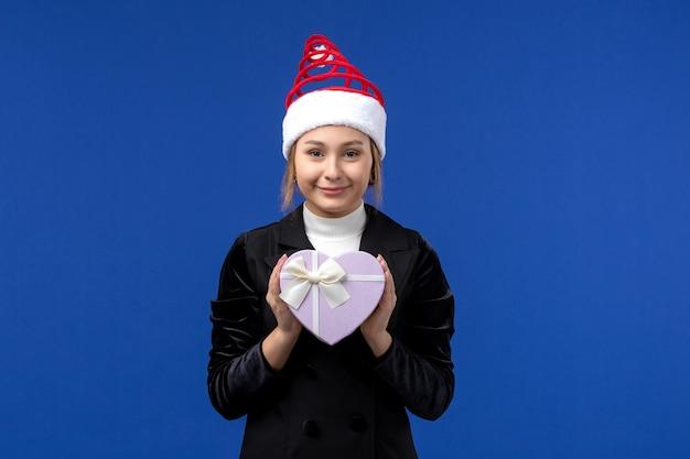 Вид спереди молодая дама держит подарок в форме сердца на синей стене новогодний праздник эмоций