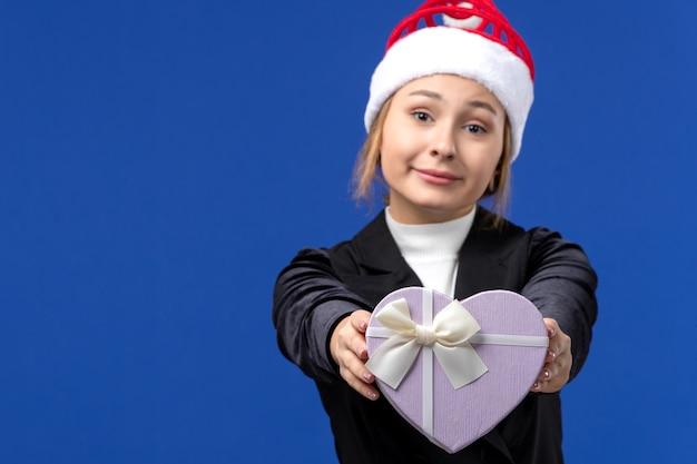 青い壁の新年のギフトの休日にハート型のプレゼントを保持している正面図若い女性