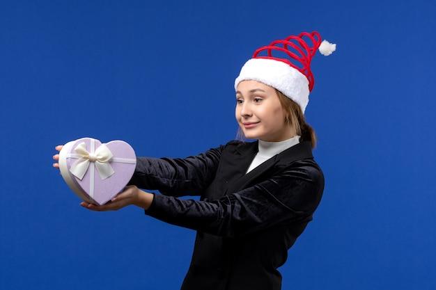 青い壁の新年の贈り物の休日にハート型のプレゼントを保持している正面図若い女性