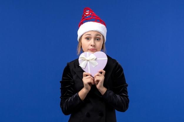 Вид спереди молодая дама держит подарок в форме сердца на синей стене новогодние подарки праздники