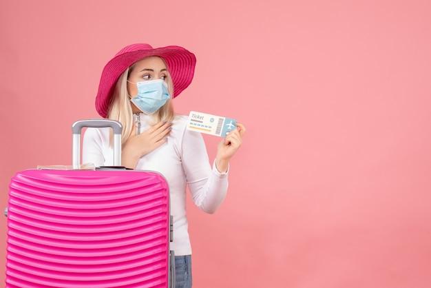 Вид спереди молодой леди, держащей билет на самолет, стоя возле чемодана
