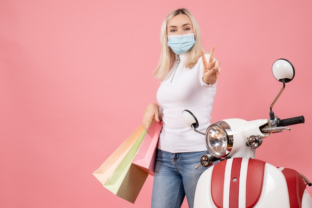 Front view young lady holding shopping bags gesturing victory sign near moped