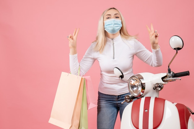 Front view young lady holding shopping bags making victory sign near moped