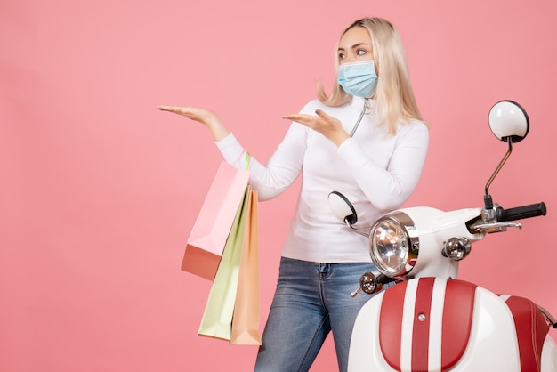 Front view young lady holding shopping bags pointing at left near moped on pink wall