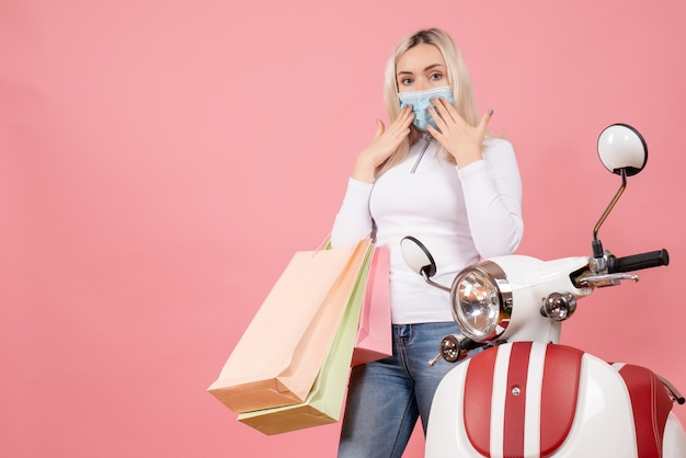 Front view young lady holding shopping bags putting hands to her face near moped
