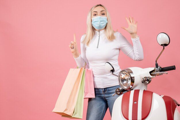 Front view young lady holding shopping bags waving hand near moped
