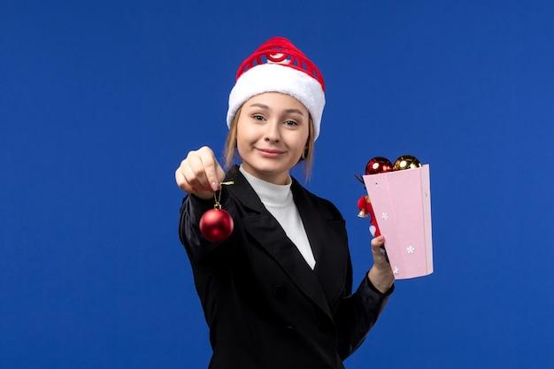 La giovane signora di vista frontale che tiene i giocattoli dell'albero sul blu di festa del nuovo anno di emozione della parete blu