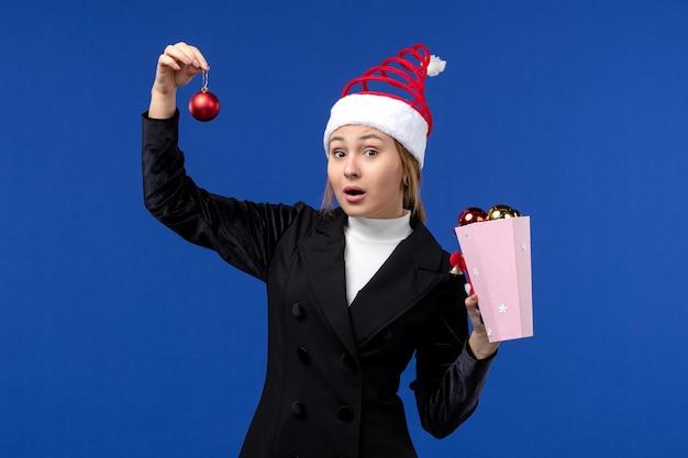 Вид спереди юная леди держит елочные игрушки на синей стене синие эмоции новогодний праздник