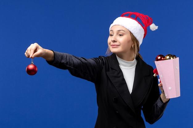 Вид спереди молодая леди, держащая елочные игрушки на синей стене, эмоция, новогодние праздники, синий