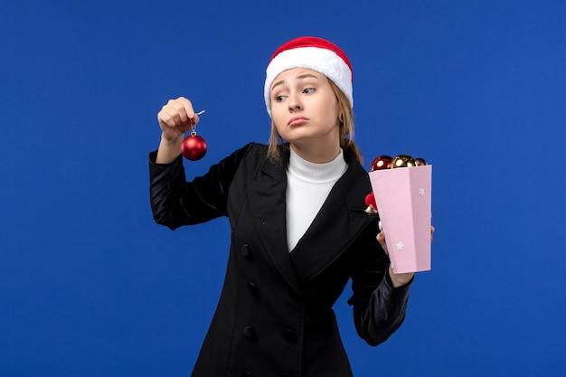 青い壁の感情新年休日青に木のおもちゃを保持している正面図若い女性