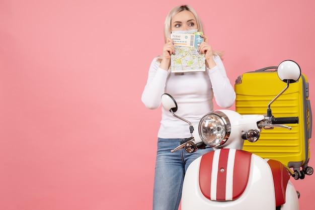 Вид спереди молодая дама, держащая билет и карту на лице, стоящая возле мопеда