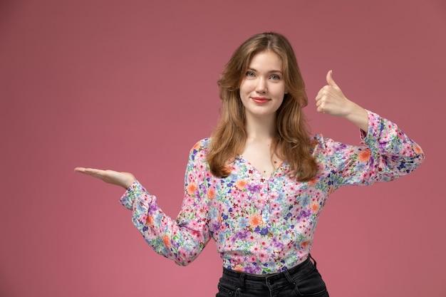 La giovane signora di vista frontale illustra i pollici in su e la mano vuota