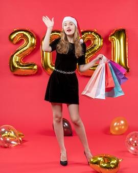 赤のショッピング バッグの風船を持って誰かを歓迎する黒のドレスを着た正面の若い女性