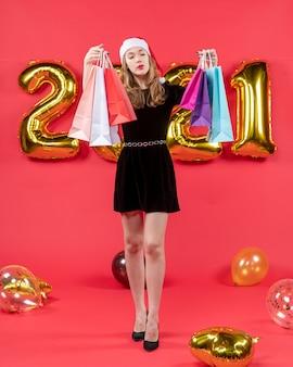 赤のショッピング バッグの風船を保持している黒のドレスを着た正面の若い女性