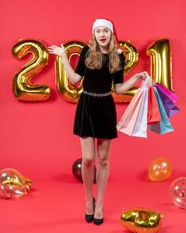 Вид спереди молодая дама в черном платье держит воздушные шары для покупок на красном