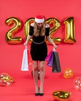 赤の床の風船を見て買い物袋を保持している黒のドレスを着た正面の若い女性