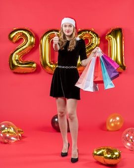 赤のサイン風船を親指を作るショッピング バッグを保持している黒のドレスを着た正面の若い女性