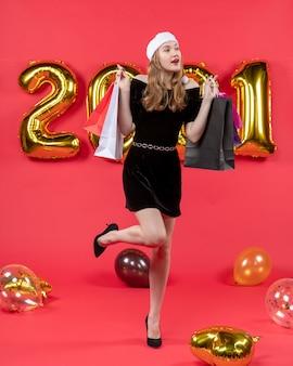 赤の足の風船を上げる買い物袋を保持している黒のドレスを着た正面の若い女性