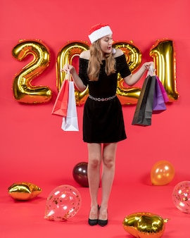 빨간색 쇼핑백 풍선보고 검은 드레스에 전면보기 젊은 아가씨