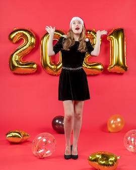 赤の手の風船を開いて見上げる黒いドレスを着た正面の若い女性