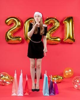 赤の床の風船に shh サイン バッグを作る黒のドレスを着た正面の若い女性