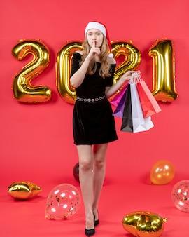 赤のショッピング バッグの風船を保持している shh サインを作る黒のドレスを着た正面の若い女性