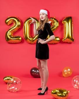赤の腰の風船に手を入れて黒のドレスを着た正面の若い女性