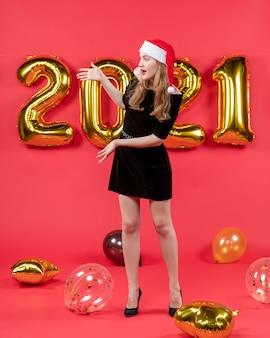 赤に何か風船を示す黒いドレスを着た正面の若い女性