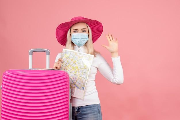 手を振って地図を保持しているスーツケースの近くに立っているマスクの正面図若い女性