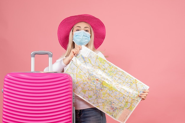 Front view young lady in mask standing near suitcase holding map