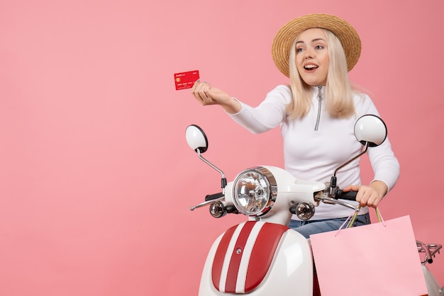 Front view young lady on moped giving card holding shopping bags