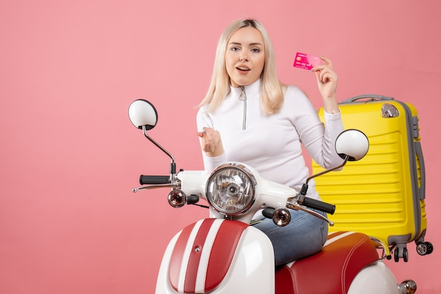 Front view young lady on moped holding card making money sign