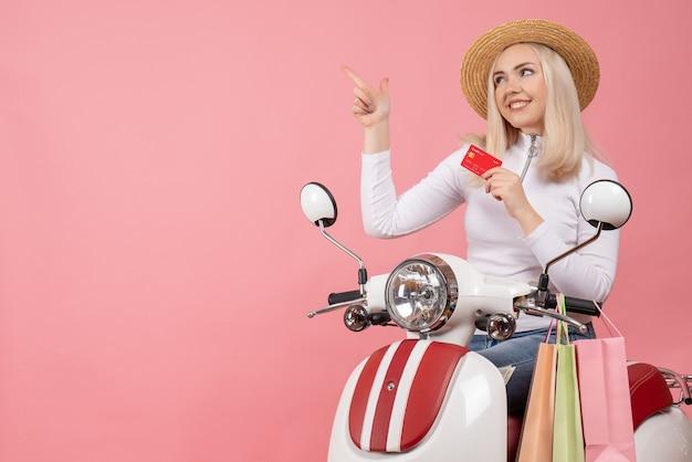 Giovane signora di vista frontale sulla carta della tenuta del ciclomotore che indica a sinistra