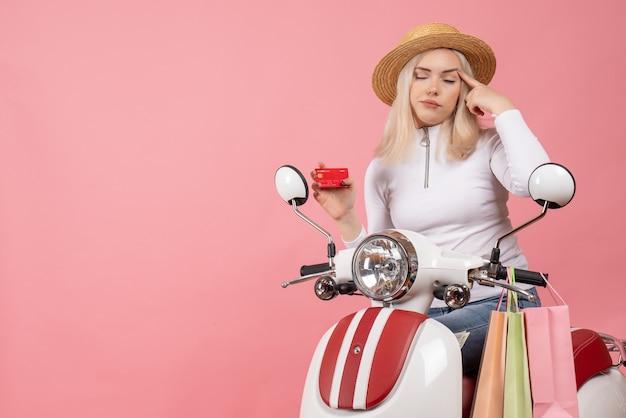 Giovane signora di vista frontale sulla carta di credito della holding del ciclomotore