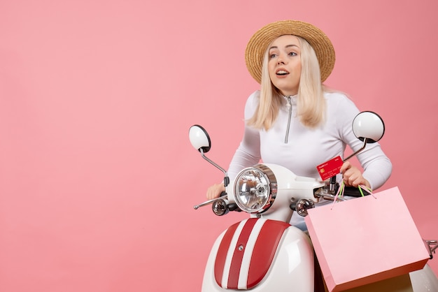 Front view young lady on moped holding shopping bags and card